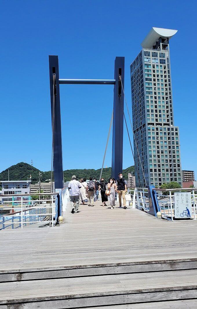 門司港にある「ブルーウィング橋」が閉まって、通行する人達