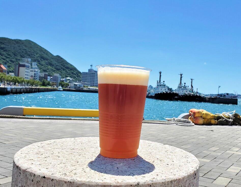 門司港地ビール工房の地ビールを門司港を背景にして眺める