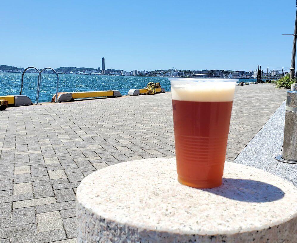 門司港地ビール工房の地ビールを門司港を背景にして眺める-1