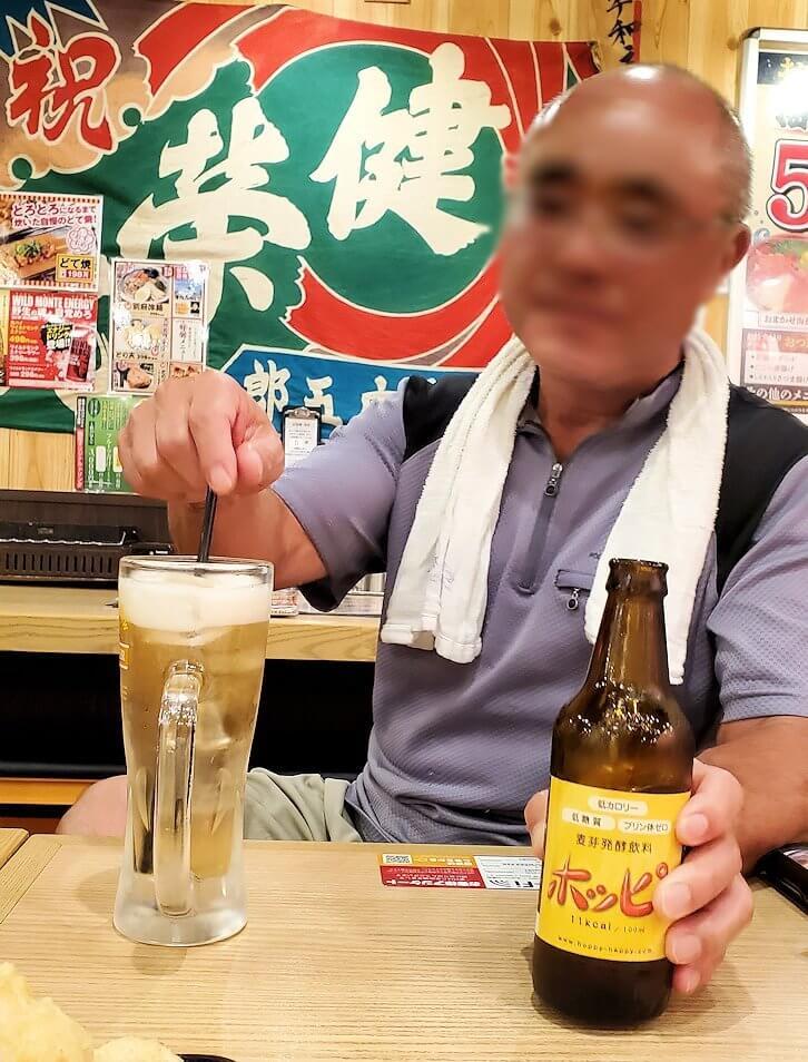 夜の別府で居酒屋に入り、ホッピーを飲むオジサン