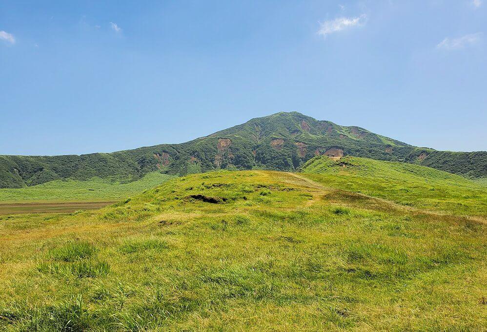 阿蘇の草千里ヶ浜の丘に立って、その景色を眺める-1