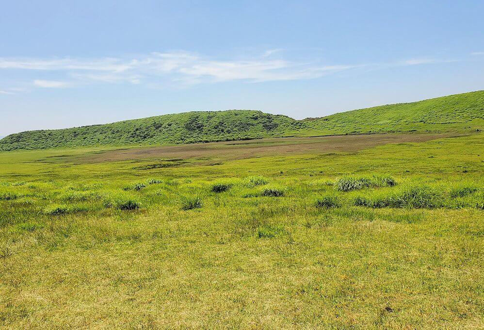 阿蘇の草千里ヶ浜の丘を歩いて進む