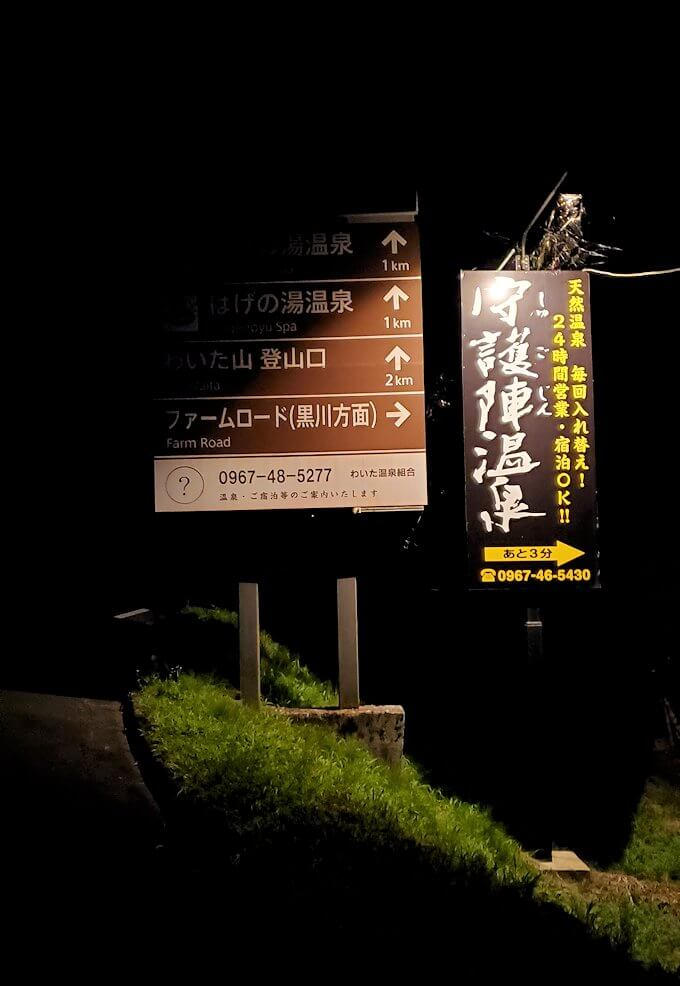 暗闇の中に光る温泉宿の看板