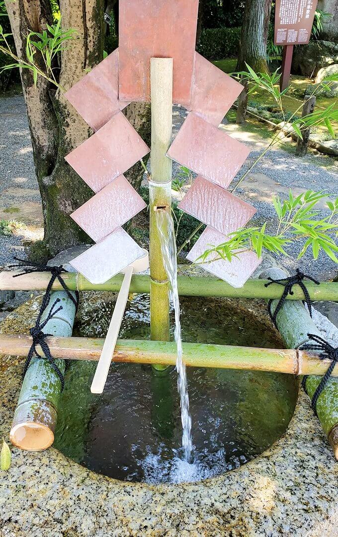 水前寺成趣園内の石橋から庭園にある長寿の水-1