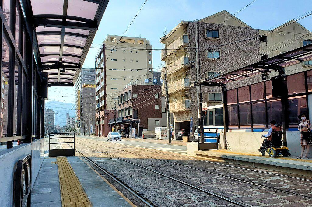 熊本市内の路面電車駅で電車を待つ