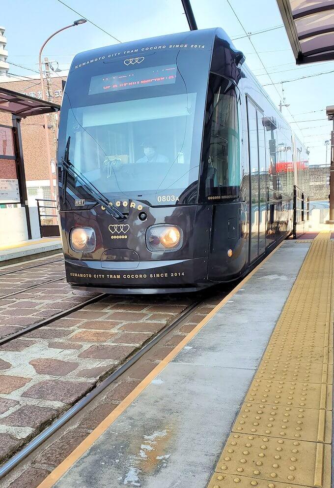 熊本市内の路面電車駅で電車が到着