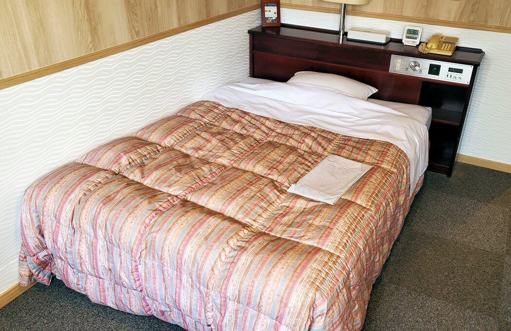「ホテル&レジデンス南州館」のシングルルームのベッド