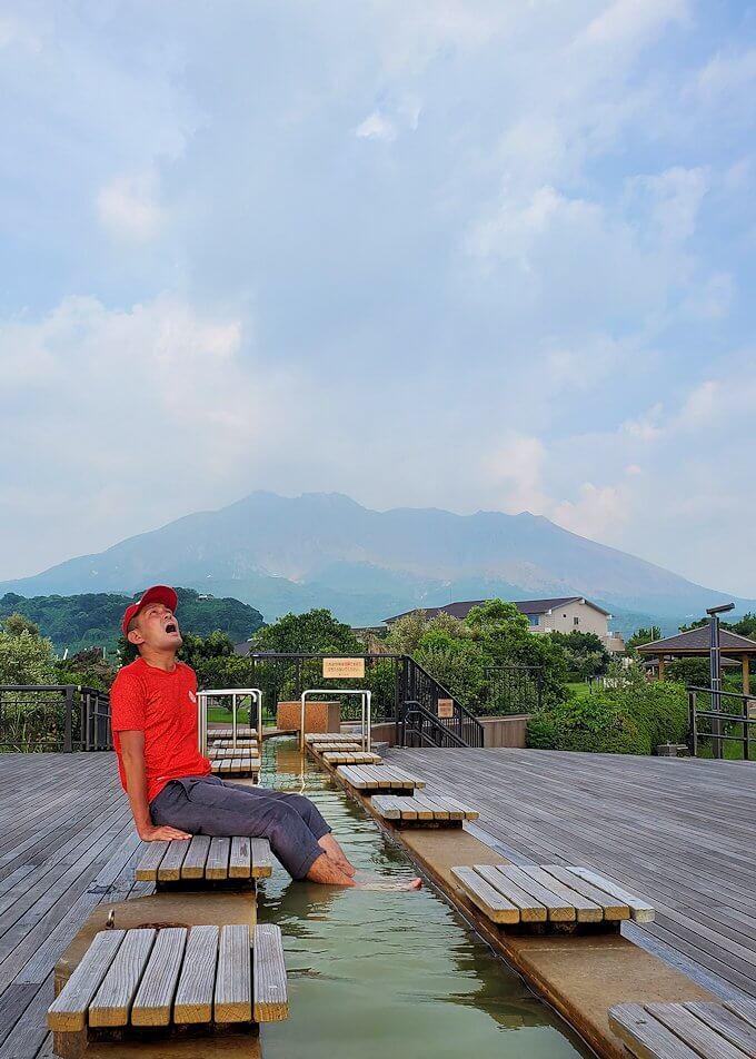 桜島溶岩なぎさ公園の足湯に浸かる男