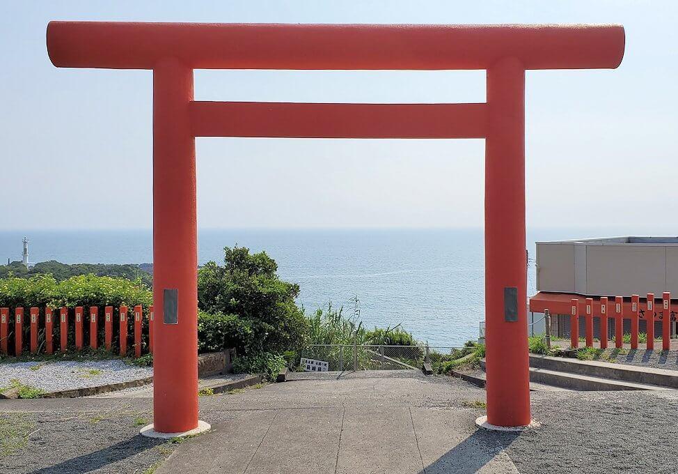 長崎鼻にある龍宮神社の鳥居から海を眺める