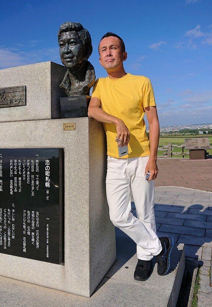 「さっぽろ羊ヶ丘展望台」にある、「恋の街札幌」の石原裕次郎胸像と肩を並べる男