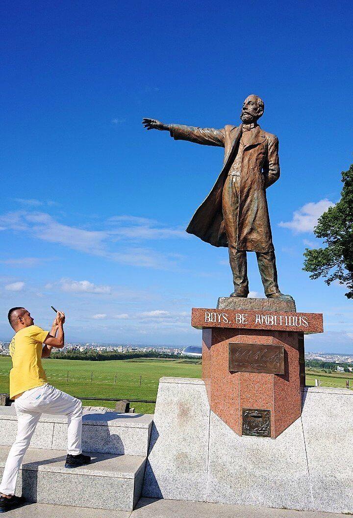 「さっぽろ羊ヶ丘展望台」にあるクラーク博士の像の右手を写真に収める男