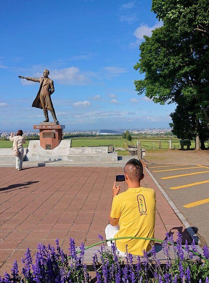 さっぽろ羊ヶ丘展望台に立つクラーク博士像を写真に収める男