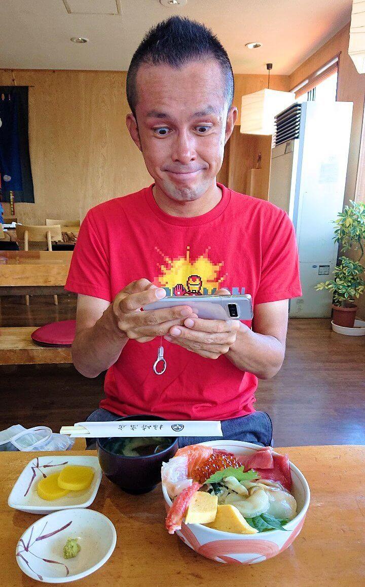 余市駅近くにある「海鮮工房」で注文した海鮮丼を写真に撮る男