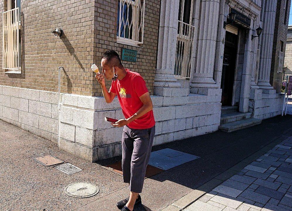 小樽の街にある、47銀行の建物前でアイスクリームを食べる男
