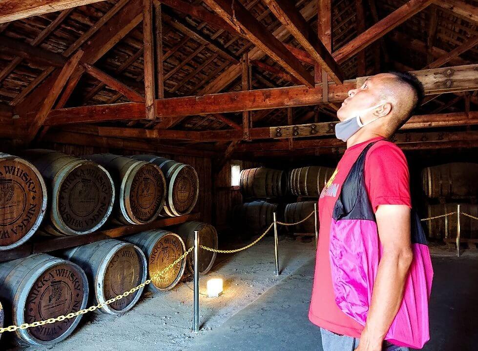 ニッカウヰスキー余市蒸留所内ある貯蔵庫の内観で臭いを嗅ぐ
