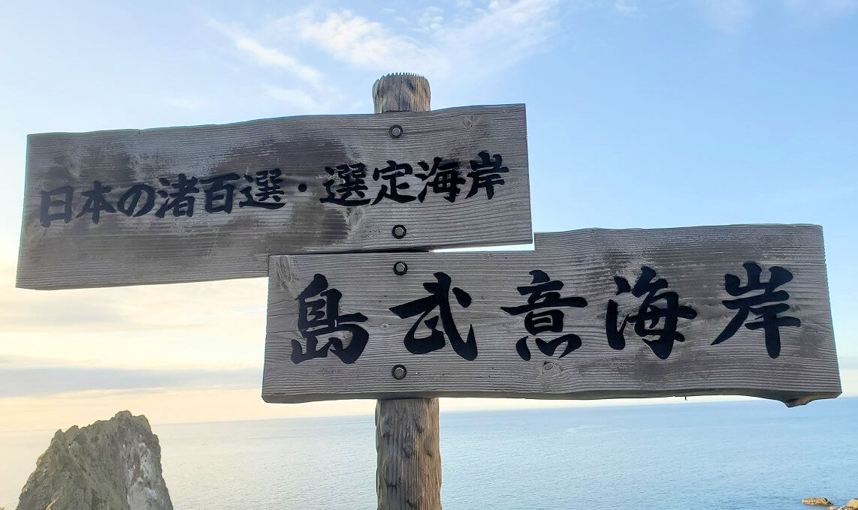 夕暮れ時の「島武意海岸」の看板