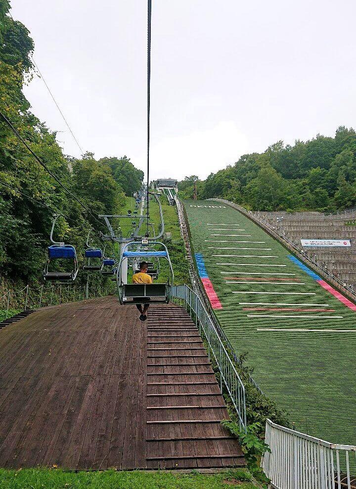 大倉山ジャンプ競技場のリフトで昇る男