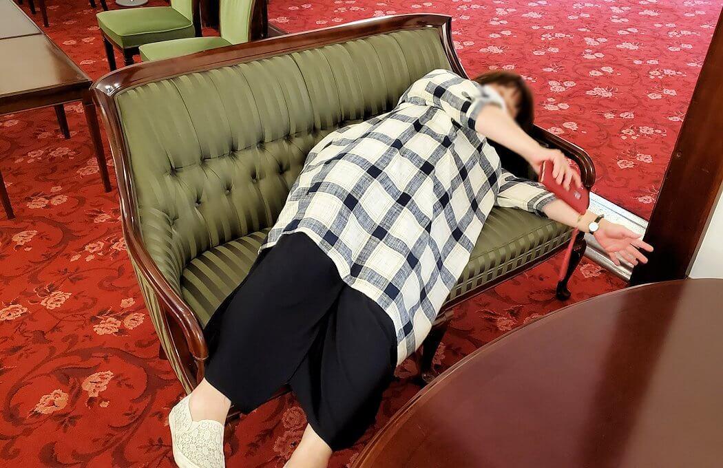 豊平館1階の会食場広間の椅子に横たわる女性